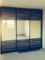 Sliding robe with gloss and wood panels - bedroom units designed and fitted by Barrett Kitchens, Donegal, Ireland